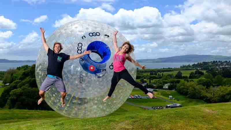 People jumping in front of a Zorb